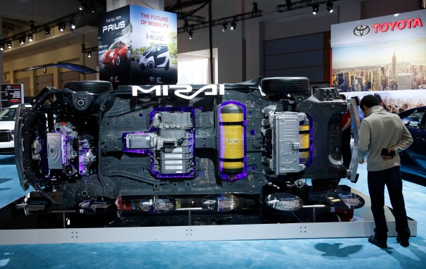 Visitor looks at underside components of Toyota Mirai hydrogen fuel cell vehicle at the Washington Auto Show in Washington